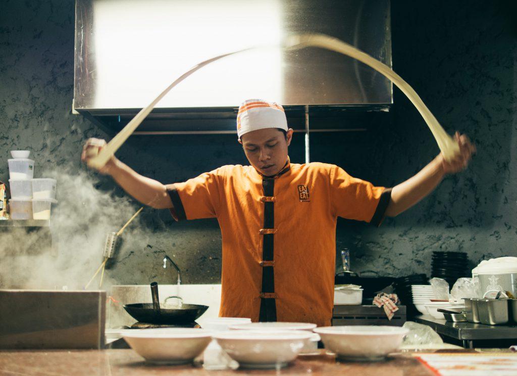 cook making pasta